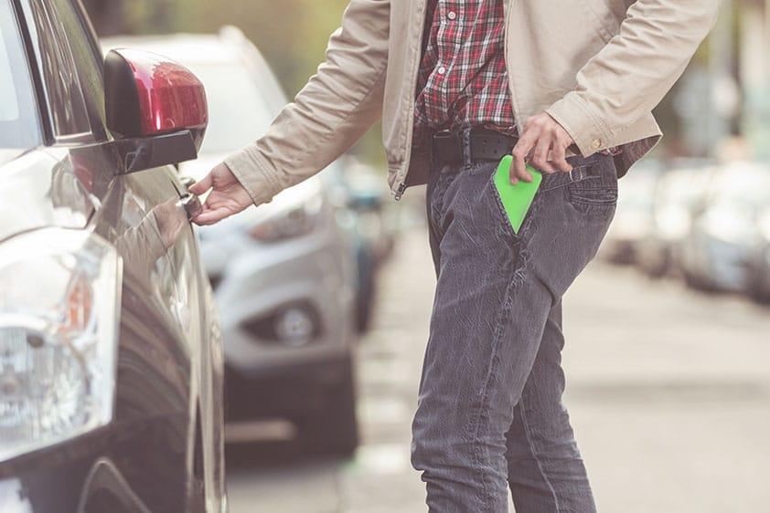 homme qui rentre dans un auto après avoir mis son cellulaire dans sa poche