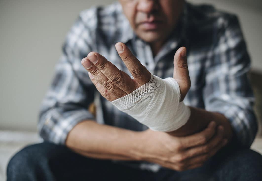 man with manual trauma, gauze bandage around hand