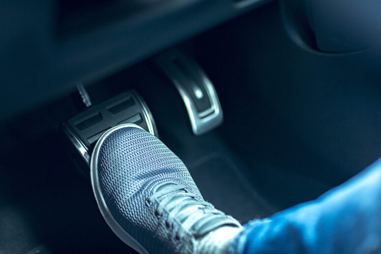 foot pressing against a car's brake pedal to slow down
