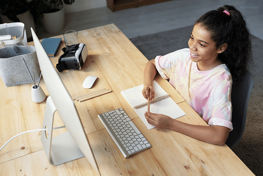 teenage girl looking at a computer monitor and smiling, with a notebook and pencil in front of her